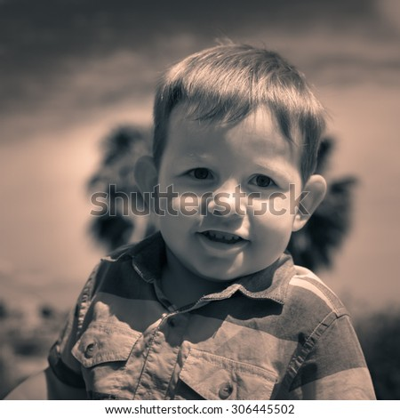 Portrait of cute smiling child boy outdoors. - stock photo