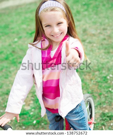 Portrait of Cute smiling little girl on bicycle with thumbs up - stock photo