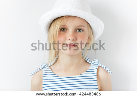 Portrait of cute smiling little girl wearing striped dress and white hat looking with cheerful expression at the camera. Cute stylish blonde preschool kid against white wall. Happy childhood concept - stock photo