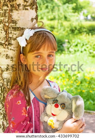 Portrait of cute smiling little girl with a toy in her hands