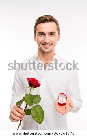 Portrait of cute smiling man, making proposal with wedding ring - stock photo