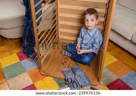 Portrait of cute son assembling with his father cot for a newborn at home. Family leisure concept