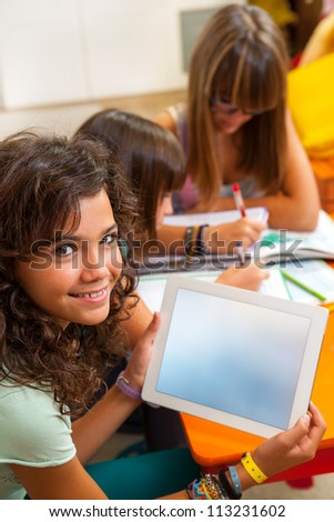 Portrait of cute student holding digital tablet with free copy space.