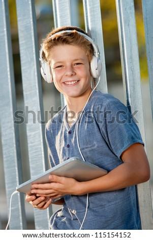 Portrait of cute teen boy holding  digital tablet outdoors. - stock photo