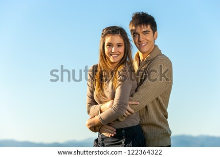 Portrait of cute teen couple embracing outdoors. - stock photo