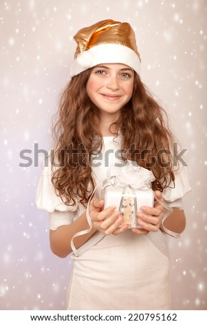 Portrait of cute teen girl with Christmas gift on snowy background, wearing funny Santa hat, celebrating New year  - stock photo