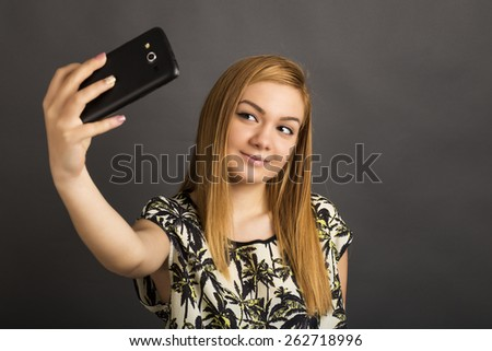 Portrait of cute teenage girl taking self portrait  with her smart phone over gray background - stock photo