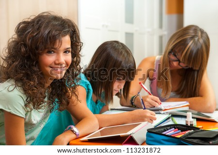 Portrait of cute teenage student doing homework with friends at home. - stock photo