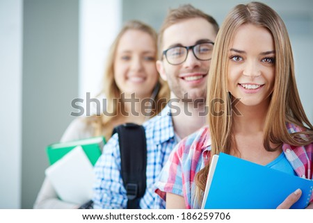 Portrait of cute teenager looking at camera with her friends behind - stock photo