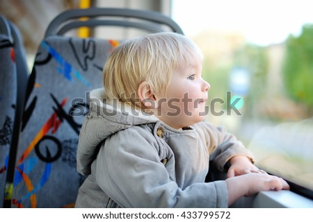 Portrait of cute toddler boy looking out train or tram window - stock photo