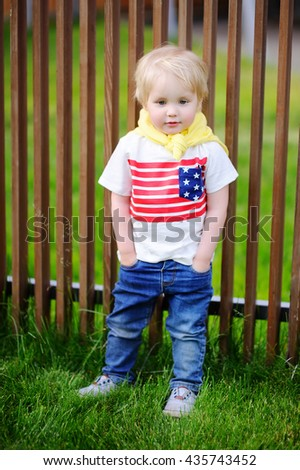 Portrait of cute toddler boy posing outdoors at the sunny summer day