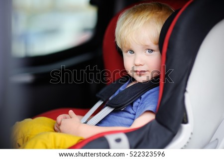Portrait of cute toddler boy sitting in car seat. Child transportation safety