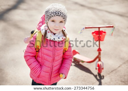 Portrait of cute toddler girl in pink jacket with the scooter - stock photo