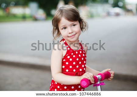 Portrait of cute toddler girl in red dress on the scooter