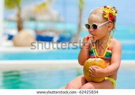 portrait of cute toddler girl with coconut cocktail in the tropical beach - stock photo