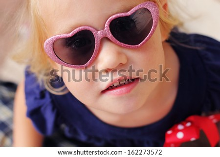 Portrait of cute 2,5 years old baby with fashion sunglasses