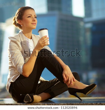 Portrait of cute young business woman outdoor with coffee cup - stock photo