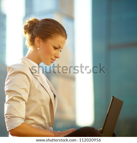 Portrait of cute young business woman outdoorwith coffee and laptop - stock photo