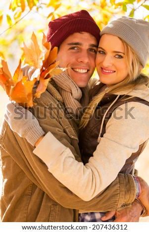 portrait of cute young couple hugging in autumn forest - stock photo