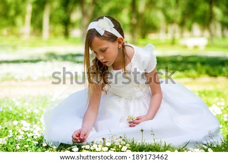 Portrait of cute young girl in white dress picking flowers in field.