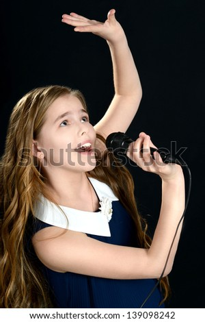 portrait of cute young girl singing on a black background - stock photo