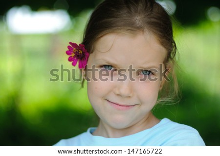 Portrait of cute young girl with flower - stock photo
