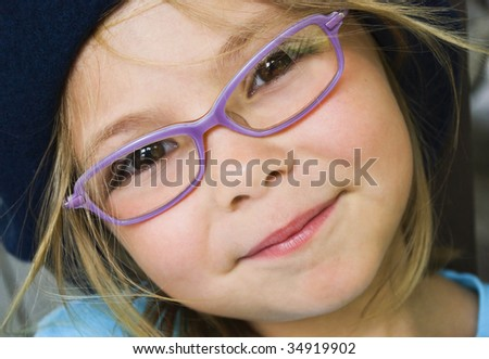 Portrait of cute young schoolgirl with glasses smiling at camera