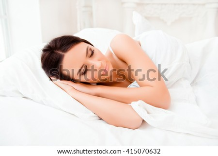 Portrait of cute young woman sleeping in white bed