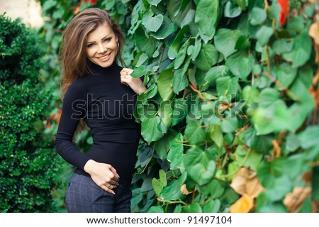 Portrait of cute young woman standing near green fence - stock photo