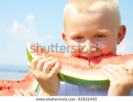 Portrait of cutelittle boyl with peace of red watermelon on blue sky background