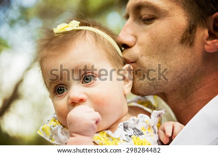 portrait of dad embracing with soft kiss for daughter with shallow depth of field on daughter - stock photo