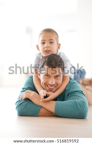 Portrait of daddy and son laying on floor