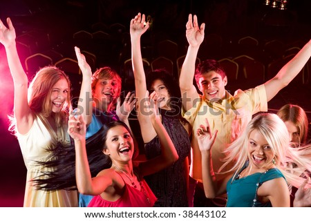 Portrait of dancing people raising hands and laughing