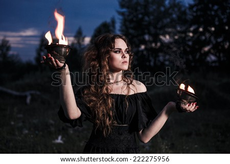 Portrait of dangerous woman witch with fire ball and dark make up - stock photo