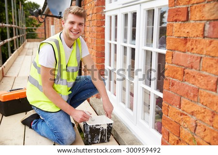 Portrait Of Decorator On Scaffolding Painting House Windows - stock photo
