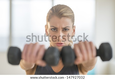 Portrait of dedicated young woman lifting dumbbells at health club