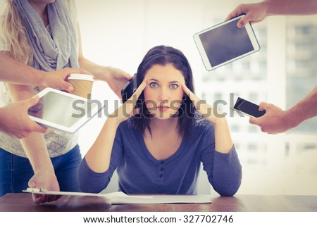 Portrait of depressed businesswoman with head in hand while sitting at desk - stock photo