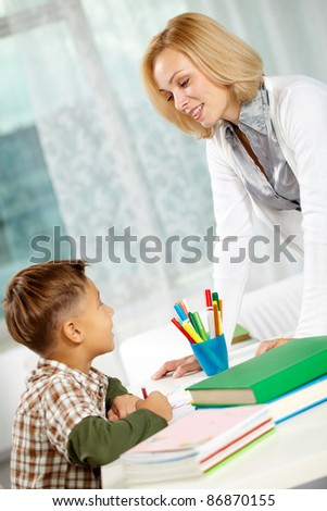 Portrait of diligent boy drawing at home and his tutor looking at each other - stock photo