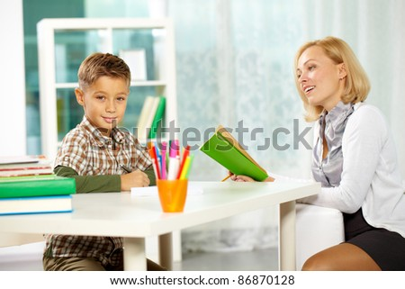 Portrait of diligent boy looking at camera at workplace with his tutor sitting near by - stock photo