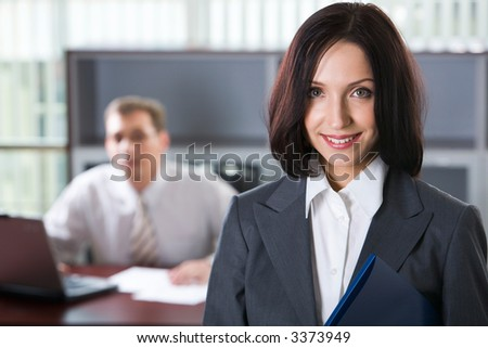 Portrait of diligent businesswoman with the blue document case in her hands and a man working on the laptop on the background
