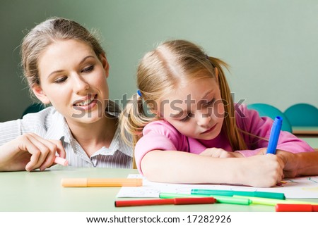 Portrait of diligent girl drawing something under tending of her teacher