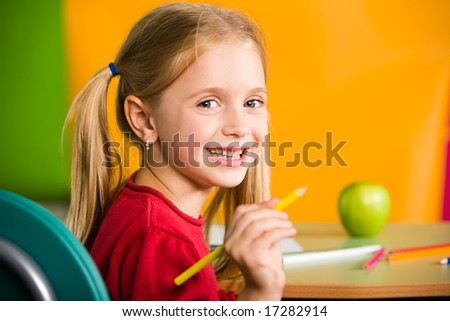 Portrait of diligent schoolgirl with pencil looking at camera during lesson - stock photo