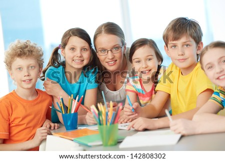 Portrait of diligent schoolkids and successful teacher looking at camera - stock photo