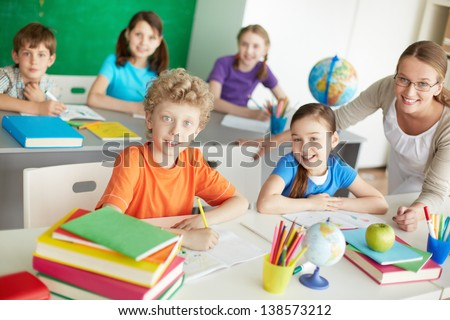 Portrait of diligent schoolkids and teacher looking at camera at lesson