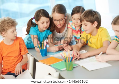 Portrait of diligent schoolkids and their teacher interacting at lesson