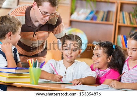 Portrait of diligent schoolkids and their teacher talking at lesson  - stock photo