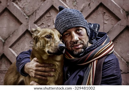 Portrait of dirty tramp hugging his dog. Image with toning and selective focus - stock photo