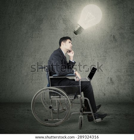 Portrait of disabled young businessman sitting on wheelchair while using laptop and looking up at light bulb - stock photo