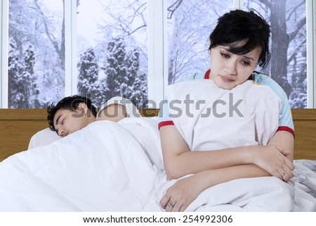 Portrait of disappointed woman sitting on the bedroom near her husband - stock photo