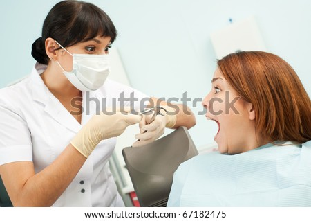 portrait of doctor and scared patient at dentist's office